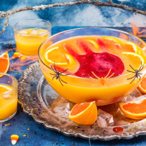 Ghoul's orange punch with bloody ice hand in a glass bowl on dark halloween background